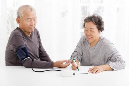 heureux senior couple de prendre la pression artérielle dans le salon