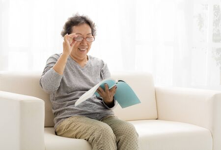 senior women: asian senior woman with book in living room Stock Photo