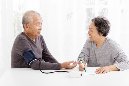 pressures: happy Senior couple taking  blood pressure in living room Stock Photo
