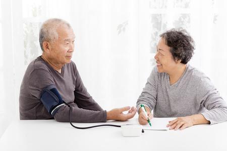 Heureux senior couple de prendre la pression artérielle dans le salon Banque d'images - 48857818