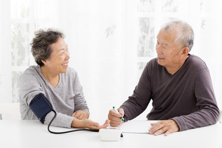 blood: happy Senior couple taking  blood pressure in living room Stock Photo