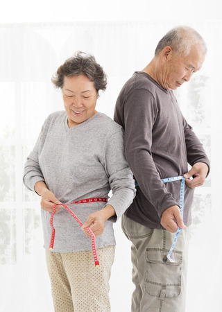 asian senior couple measuring  belly with measurement tape