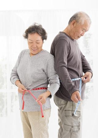 cintura: Pares asiáticos mayores Vientre de medición con cinta de medición Foto de archivo