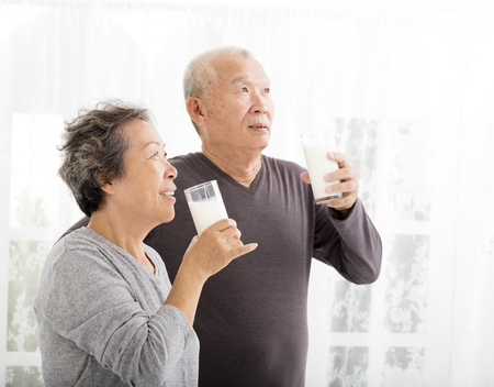 asian men: happy asian senior couple drinking milk Stock Photo