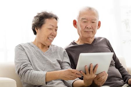 ancianos felices: Feliz pareja mayor que mira a la tableta en el sofá