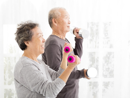 old: happy senior couple exercising with dumbbells Stock Photo