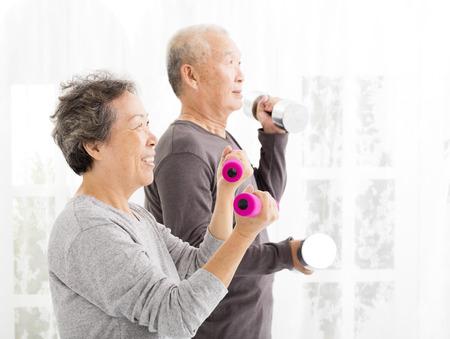 motion: lyckliga äldre par utövar med hantlar
