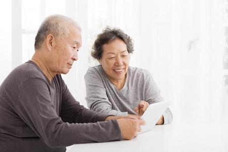 jubilados: Feliz pareja mayor que mira a la tableta en la sala de estar