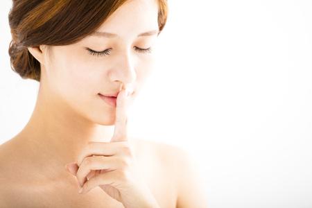 guardar silencio: hermosa mujer de cerca con el dedo en los labios