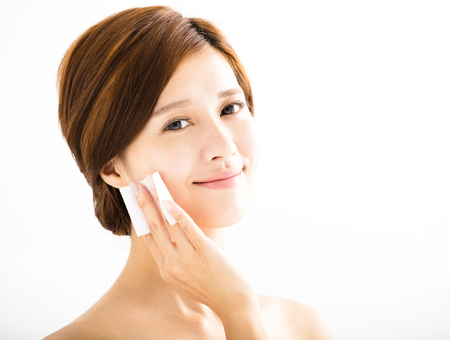 make up applying: young beautiful woman cleaning face by cotton Stock Photo