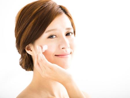 volti: sorridente donna applicazione lozione crema sul viso Archivio Fotografico