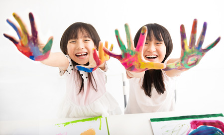 young students: happy little girls with hands in the paint Stock Photo