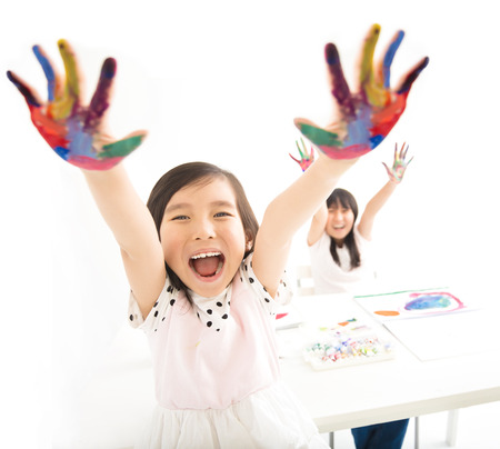 face paint: happy little girls with hands in the paint Stock Photo