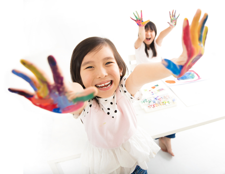 funny people: happy little girls with hands in the paint Stock Photo