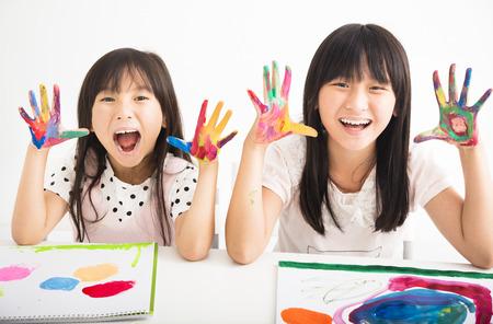 happy little girls with hands in the paint Foto de archivo