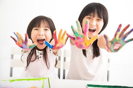 jovenes estudiantes: niñas felices con las manos en la pintura