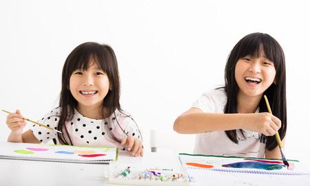children studying: ni�os felices que pintan en el aula Foto de archivo