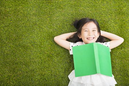 Pequeña muchacha feliz con el libro y descansando en la hierba Foto de archivo - 49363926