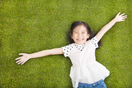 lying on grass: happy Little  girl resting on the grass Stock Photo