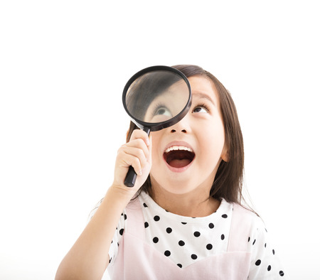 asian girl face: little girl looking through a magnifying glass