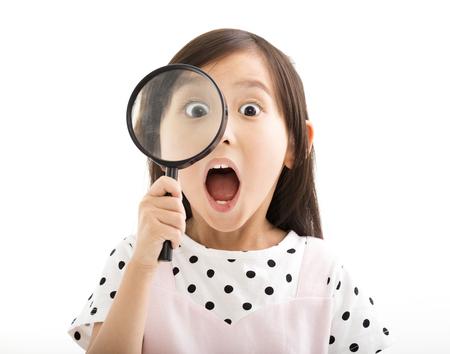 sorprendido: niña mirando a través de una lupa