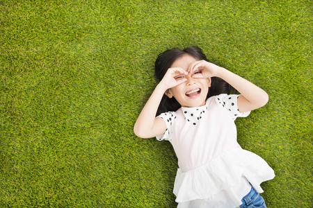 natur: Glückliches kleines Mädchen mit der Suche Geste auf dem Rasen