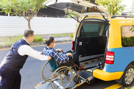 driver helping man on wheelchair getting into taxi. Stock Photo