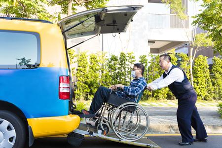 bestuurder helpt de mens op rolstoel krijgen in de taxi Stockfoto