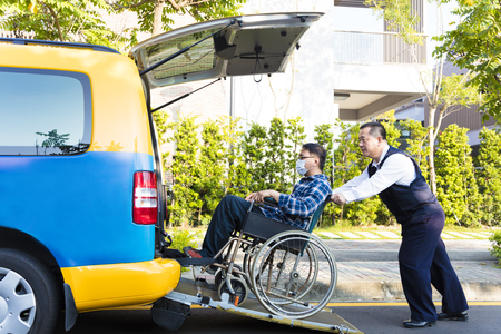 driver helping man on wheelchair getting into taxi photo