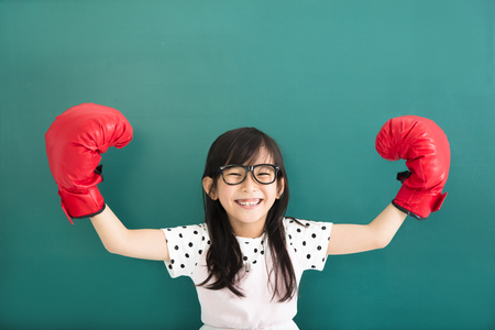 happy little girl with red boxing gloves before chalkboard Stockfoto