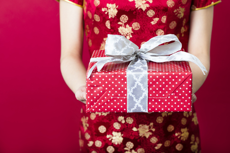young woman holding gift box on red background Stock Photo
