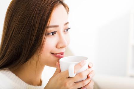 tomando café: Mujer joven bebiendo café y sentarse en el sofá