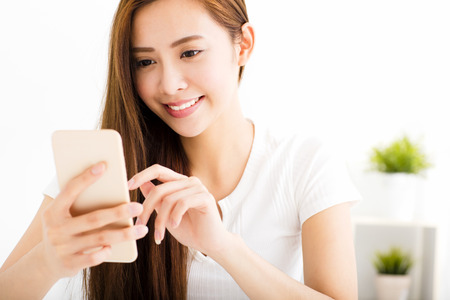 hand with phone: young beautiful woman reading message with smart phone