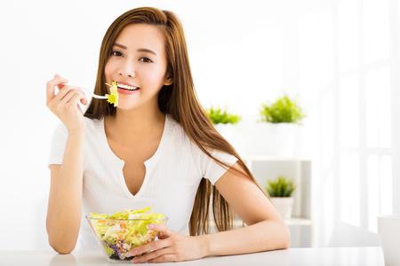ensalada de verduras: hermosa mujer joven que come la comida sana Foto de archivo
