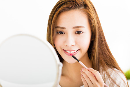 beautiful young woman putting on red lipstick 스톡 콘텐츠