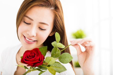 beautiful young woman with red rose in living room Stock Photo