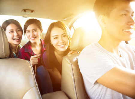 young group people enjoying road trip in the car