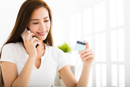 woman credit card: young woman talking on the phone and showing  credit card