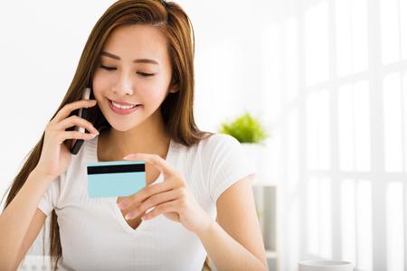 Jonge vrouw praten over de telefoon en met creditcard