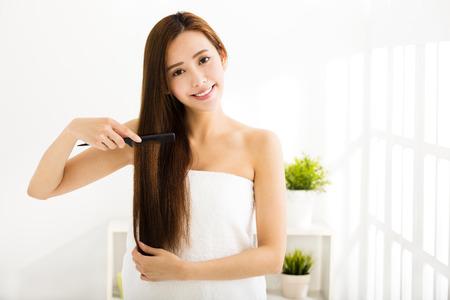 pelo largo: joven y bella mujer peinándose en el salón Foto de archivo