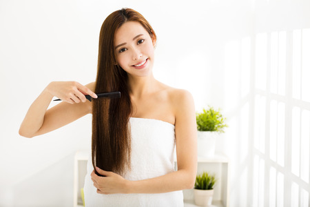 comb hair: young beautiful woman combing her hair  in living room Stock Photo