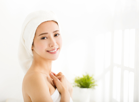 towel: smiling young woman with a towel on her head after bath Stock Photo