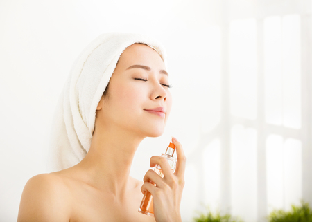 Young beautiful woman applying perfume after bath