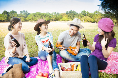 company party: happy young friends enjoying picnic and playing ukulele
