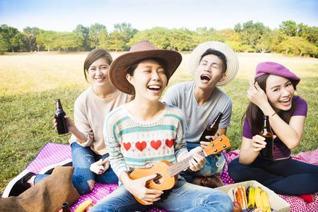 szczęśliwy młodych przyjaciół korzystających piknik i odtwarzanie ukulele