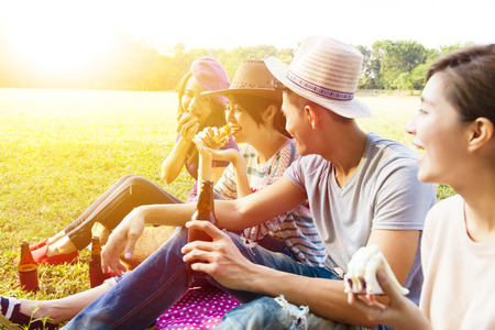 GROUP TRAVEL: happy young friends enjoying picnic and eating