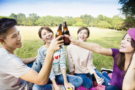 jovenes tomando alcohol: amigos jóvenes felices disfrutando de picnic y bebiendo cerveza Foto de archivo
