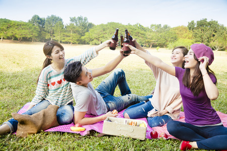 happy young friends enjoying picnic and drinking beer