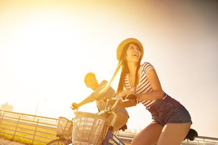 silueta ciclista: feliz pareja de jóvenes va para el paseo en bicicleta en un día soleado Foto de archivo