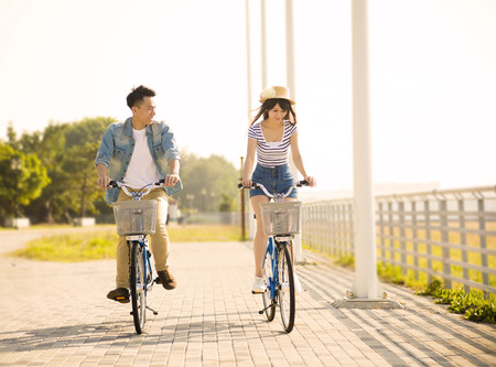 asian sport: happy young couple riding on bicycle in city park